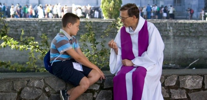 A person going to confession in Lourdes, France.